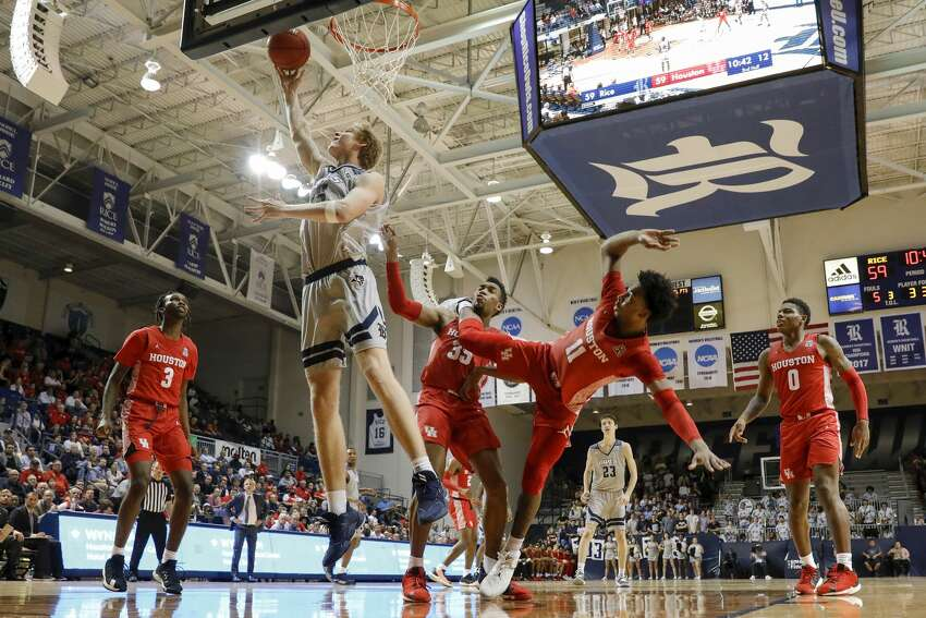 Rice Owls forward Max Fiedler (15) goes up for a lay up defended by Houston Cougars forward Fabian White Jr. (35) and guard Nate Hinton (11) during the second half of the NCAA basketball game between the Rice Owls and the Houston Cougars at Tudor Fieldhouse in Houston, TX on Tuesday, November 19, 2019. The Cougars defeated the Owls 97-89.