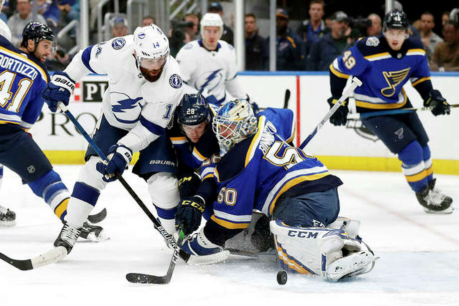 Tampa Bay's Pat Maroon (14) is unable to score past Blues goaltender Jordan Binnington and Mackenzie MacEachern (28) Tuesday night in St. Louis. Maroon, who played for the Blues last season and was a fan favorite, was presented his Stanley Cup championship ring by the Blues prior to Tuesday's game.