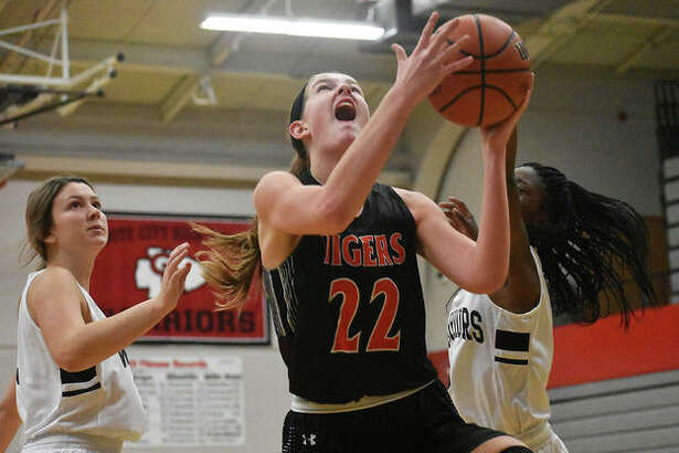Edwardsville's Katelynne Roberts goes up for a layup between two Granite City defenders in the first quarter.