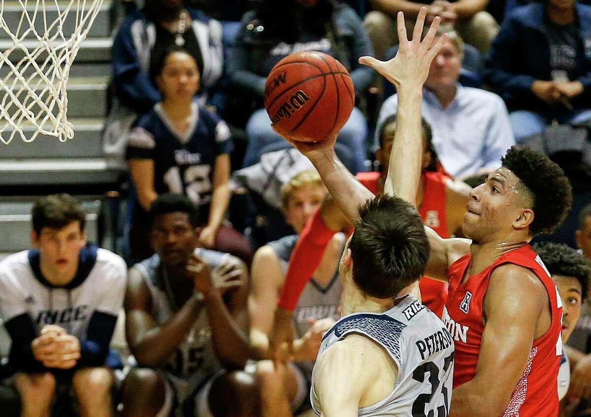 Resorting to underhanded means, UH guard Quentin Grimes, right, takes the ball to the bucket while defended by Rice guard Drew Peterson on Tuesday night at Tudor Fieldhouse. Grimes scored a game-high 32 points in the Cougars' 97-89 victory.