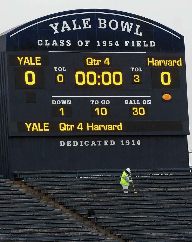 A worker cleans under the scoreboard at Yale Bowl as contractors and Yale employees ready the stadium for the big match-up against Harvard in 2011. Photo: File Photo