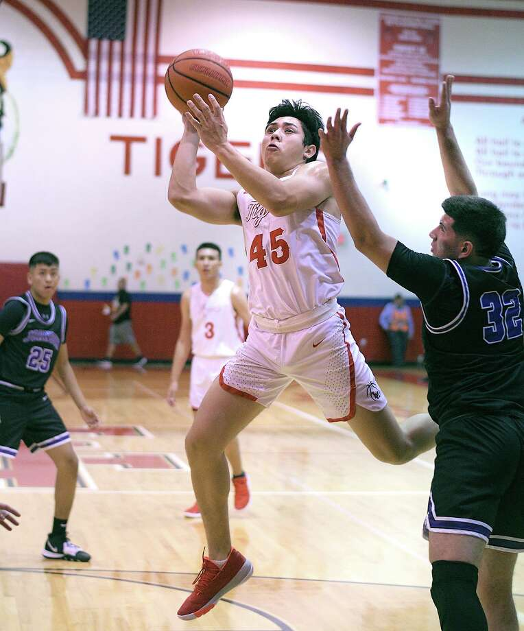 Winder Vasquez drives to the basket for the Martin Tigers as Billy Rodriguez defends for the LBJ Wolves Tuesday, November 19, 2019 at the Roberto J. Flores Gymnasium at Martin High School. Photo: Cuate Santos / Laredo Morning Times / Laredo Morning Times