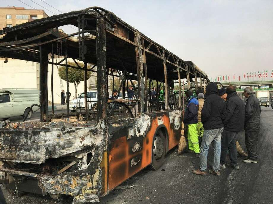 Iranians inspect a bus that was set ablaze Sunday by protesters in the city of Isfahan during a demonstration against a rise in gas prices. Photo: AFP Via Getty Images