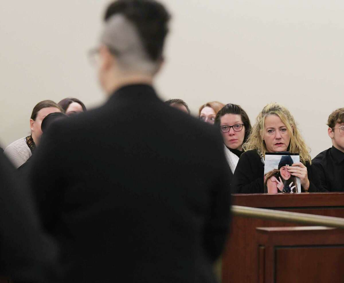 Harley Kelly, foreground, is led out of Albany County Court following her sentencing on Wednesday, Nov. 20, 2019, in Albany, N.Y. Kelly was sentenced for causing the fatal crash in June that killed her passenger and friend, Emily Tuck-Fydenkevez. Emily's mother, Susan Bartholomew-Fydenkevez, right, holds a photo of Emily. (Paul Buckowski/Times Union)