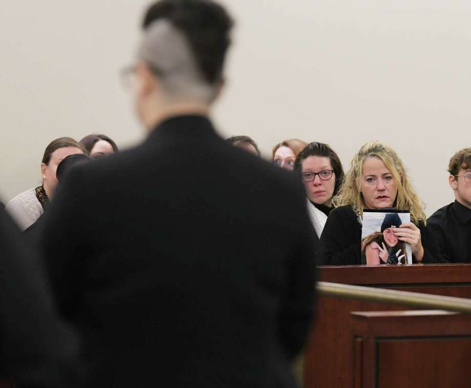Harley Kelly, foreground, is led out of Albany County Court following her sentencing on Wednesday, Nov. 20, 2019, in Albany, N.Y. Kelly was sentenced for causing the fatal crash in June that killed her passenger and friend, Emily Tuck-Fydenkevez. Emily's mother, Susan Bartholomew-Fydenkevez, right, holds a photo of Emily. (Paul Buckowski/Times Union) Photo: Paul Buckowski, Albany Times Union / (Paul Buckowski/Times Union)