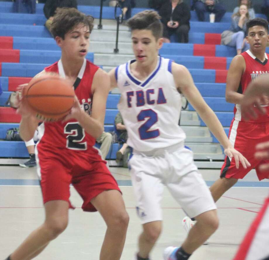 FBCA's Nick Gay applies front-court pressure on Angleton Christian's Jacob Soria during second-half action Tuesday night. Soria was the difference in the game, hitting four 3-point goals in the fourth quarter. Photo: Robert Avery