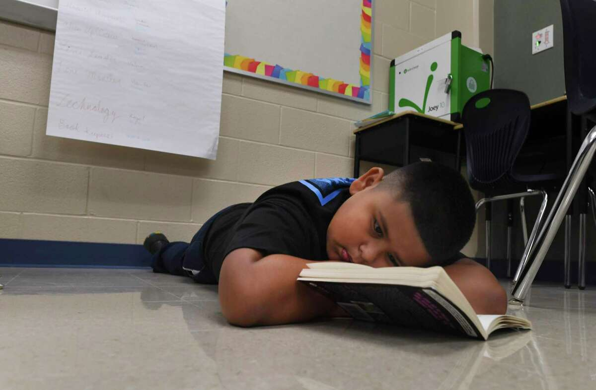 Luis Fabela enjoys a book during reading time in his fifth grade classroom at Ellison Elementary on Aug. 29, 2019.