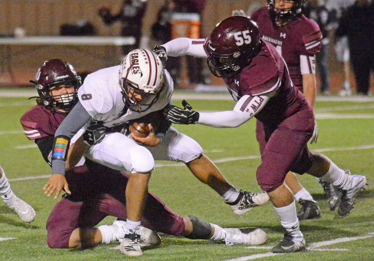 Abernathy defensive players Matthew DeAnda and Marcus Ybanez (55) team up to take down a Lubbock Roosevelt ball carrier during their District 2-3A Division II football game earlier this season in Antelope Stadium in Abernathy.