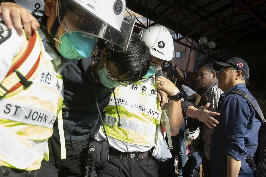 Medics help an injured protester at the Hong Kong Polytechnic University, which is at the center of demonstrations that forced a six-day shutdown of schools in the protest-scarred city. Photo: Ng Han Guan / Associated Press