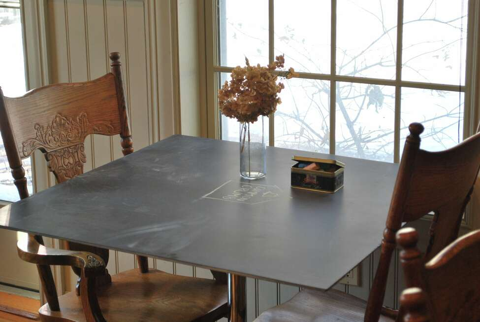Restored cafe tables made from chalkboard from the 1870s one-room schoolhouse that is now Common Crumb Artisan Bakery Craft Coffee in Brunswick, N.Y.