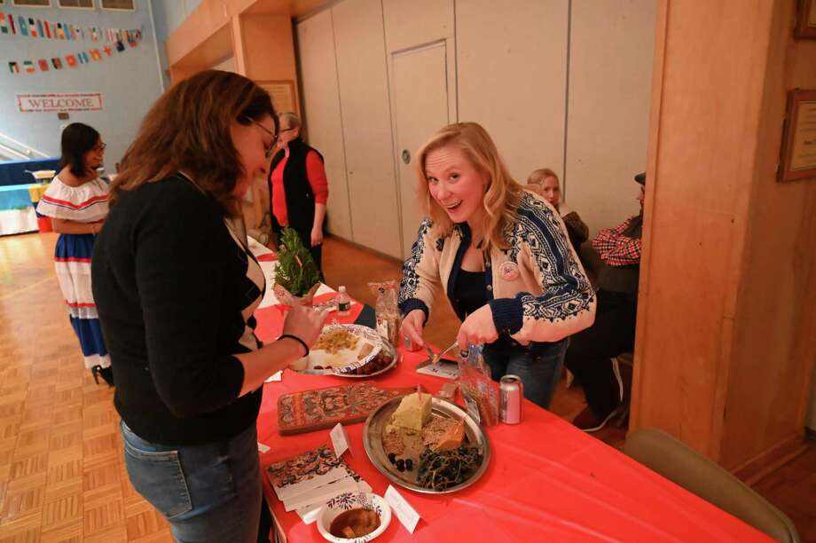 Mara Fleming, who is a member of the school board and church youth ministry serves Margaret Fleming O'Brien at Our Lady of Fatima Catholic Academy's International Family Night on Nov. 16. Photo: Gerry Davis / Our Lady Of Fatima Academy / Wilton Bulletin Contributed