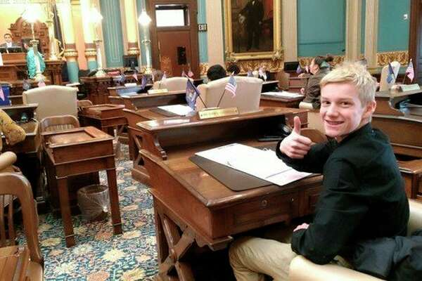 Drew Mendians who was selected as the Most Inspirational Speaker at the middle school YIG Conference is shown sitting in the seat of Sen. Curt Vanderwall in the Senate. (Courtesy photo)