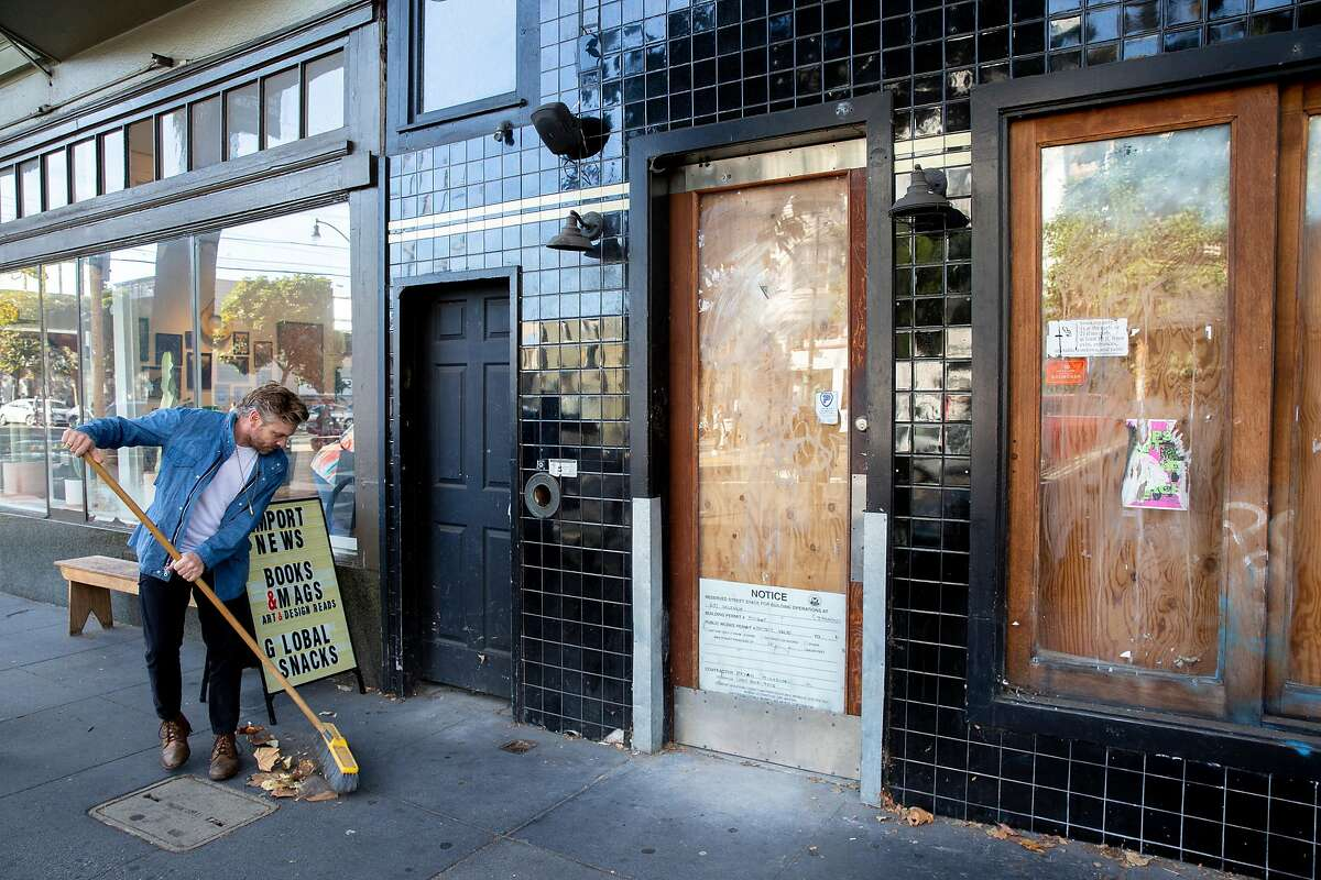 Jonah Buffa, Fellow Barber co-owner, sweeps outside the shop next to a vacated building on Saturday, Nov. 16, 2019, in San Francisco, Calif.