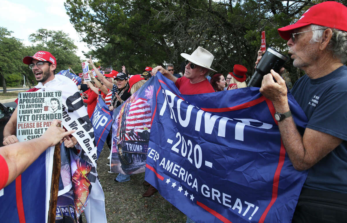 Banners dominate the pro Trump side as demonstrators line Riata Trace Parkway as President Donal Trump visits a nearby facility where Apple computers are made on Nov.20, 2019.