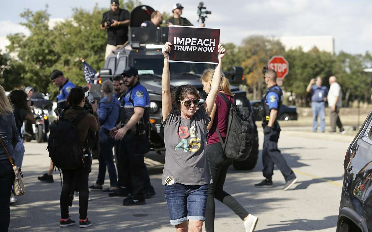 Julie Killelea stands in front of an Alex Jones vehicle as demonstrators line Riata Trace Parkway as President Donald Trump visits a nearby facility where Apple computers are made on Nov. 20, 2019.