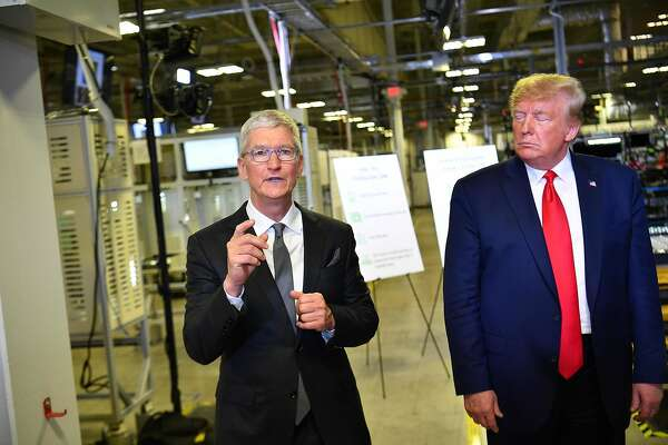 US President Donald Trump (r) and Apple CEO Tim Cook speak to the press during a tour of the Flextronics computer manufacturing facility where Apple's Mac Pros are assembled in Austin, Texas, on November 20, 2019. (Photo by MANDEL NGAN / AFP) (Photo by MANDEL NGAN/AFP via Getty Images)