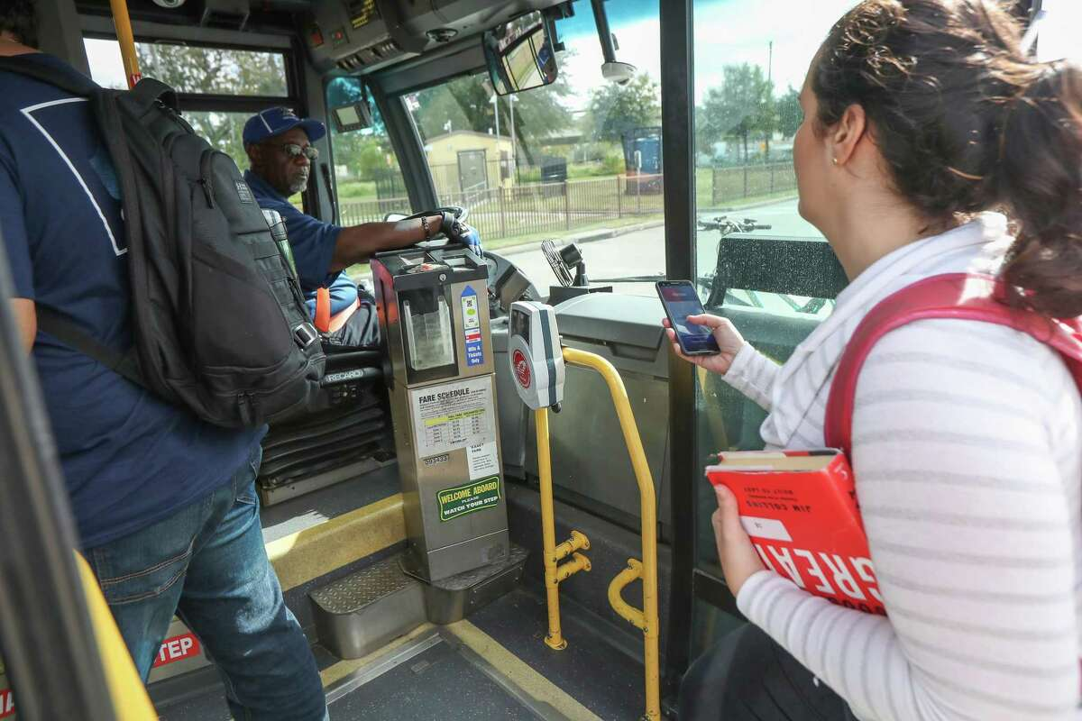 Metropolitan Transit Authority bus riders use Q cards, smartphone apps or cash to hop aboard a bus Nov. 20, 2019, in Houston. Metro is in the early steps of revamping its fare system. As part of the change, the agency is trying to phase out cash as much as possible.