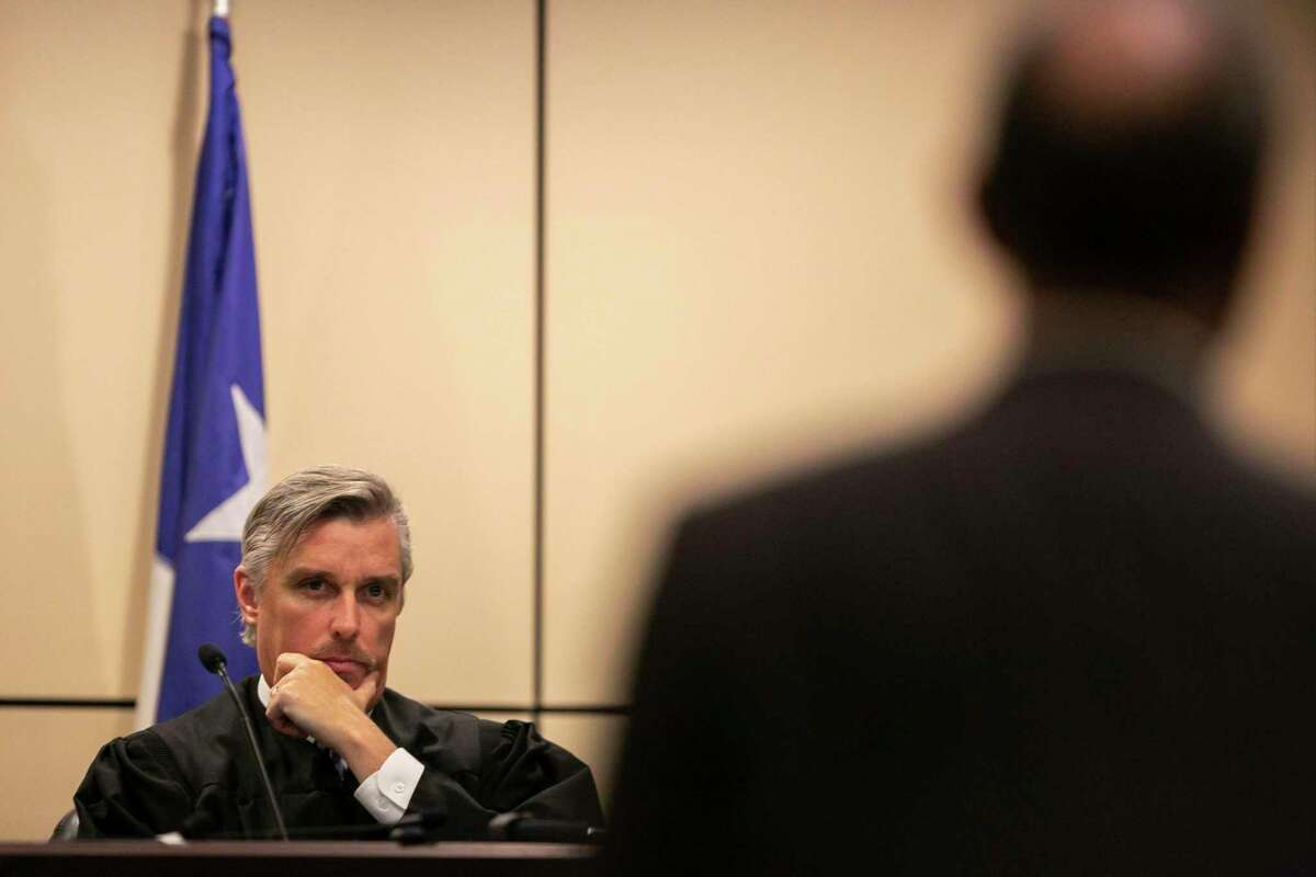 Judge Jefferson Moore of the 186th District Court listens to Prosecutor David Lunan speak during a hearing on Wednesday in the case of Emond Johnson. Johnson is accused of setting the fire that killed firefighter Scott Deem and his lawyers argued that publicity surrounding the case has made it impossible for him to receive a fair trial in San Antonio.