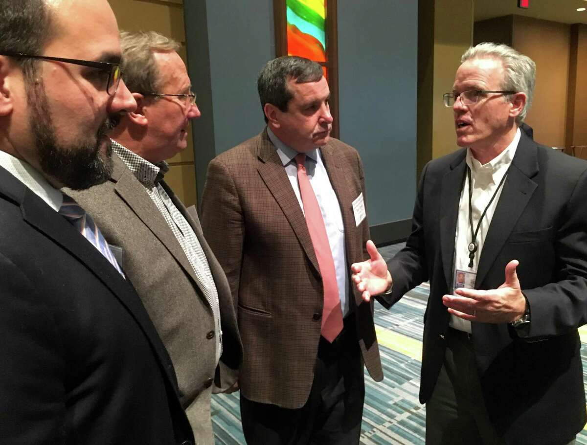 Colin Cooper, right, Connecticut's recently appointed manufacturing czar, talks with executives from the aerospace industry at the Aerospace Components Manufacturers' trade show and work force fair in Hartford Wednesday, Nov. 20, 2019.