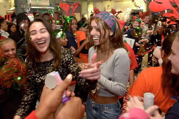 Alexandra Chakar, right, of Danbury, and her best friend Kayla Morais walk through a crowd of supporters as Chakar had her wish to go to Australia granted by Macy's, Danbury Fair mall, and Make-A-Wish Connecticut at a celebration at the store on Wednesday afternoon. Chakar, who is battling leukemia, will travel to Australia in the spring. November 20, 2019, in Danbury, Conn.