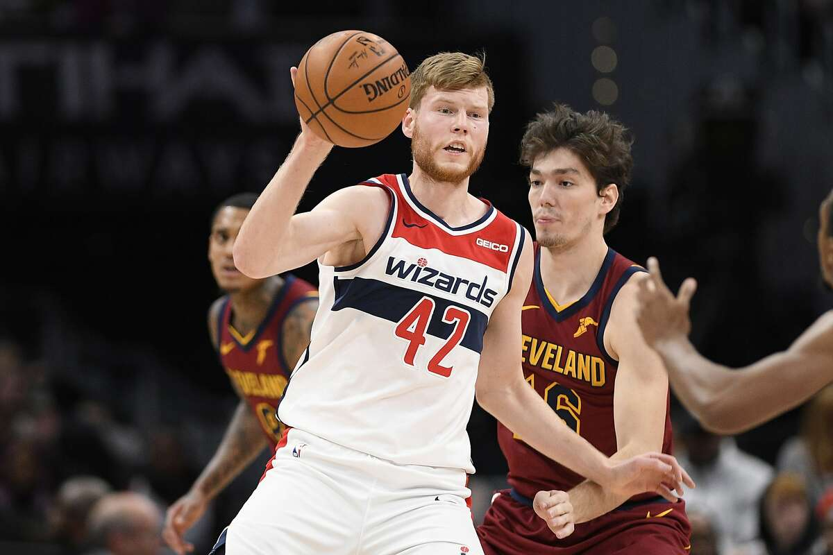 Washington Wizards forward Davis Bertans (42) looks to pass during the second half of an NBA basketball game in front of Cleveland Cavaliers forward Cedi Osman, back right, Friday, Nov. 8, 2019, in Washington. The Cavaliers won 113-100. (AP Photo/Nick Wass)