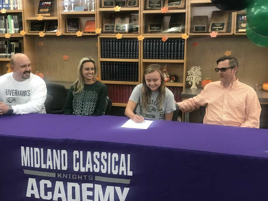 Midland Classical senior Kori Kirk signs with the Northeastern State University women's soccer program, while surrounded by family during a ceremony on Nov. 20 at MCA. Photo: Courtesy Photo