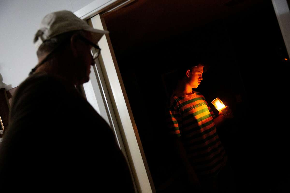 From left: William Douglas Hitt watches as his son Connor Hitt, 17, lights a candle at his home as light from a flashlight illuminates the kitchen area on Wednesday, Nov. 20, 2019, in St. Helena, Calif. The power is out at his neighborhood off of Spring Street. PG&E has shut off the power to more than 40,000 homes in an effort to prevent wildland fires.