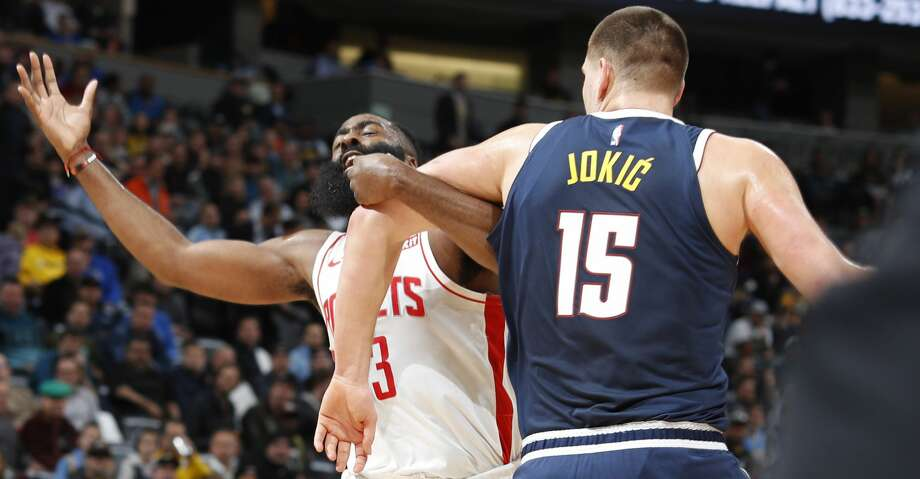 Houston Rockets guard James Harden, left, is hooked by Denver Nuggets center Nikola Jokic while driving to the rim in the first half of an NBA basketball game Wednesday, Nov. 20, 2019, in Denver. (AP Photo/David Zalubowski) Photo: David Zalubowski/Associated Press