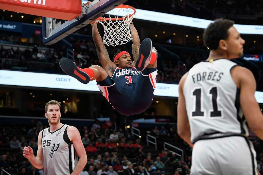 Wizards All-Star Bradley Beal hangs from the rim after dunking between the Spurs' Jakob Poeltl and Bryn Forbes. Photo: Nick Wass /Associated Press / Copyright 2019 The Associated Press. All rights reserved