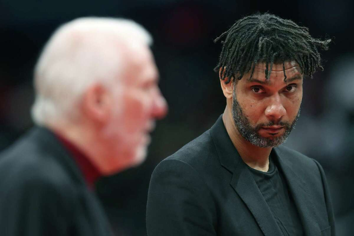 WASHINGTON, DC - NOVEMBER 20: Assistant coach Tim Duncan (R) looks on as head coach Gregg Popovich of the San Antonio Spurs talks with an official in the first half against the Washington Wizards at Capital One Arena on November 20, 2019 in Washington, DC. NOTE TO USER: User expressly acknowledges and agrees that, by downloading and/or using this photograph, user is consenting to the terms and conditions of the Getty Images License Agreement.