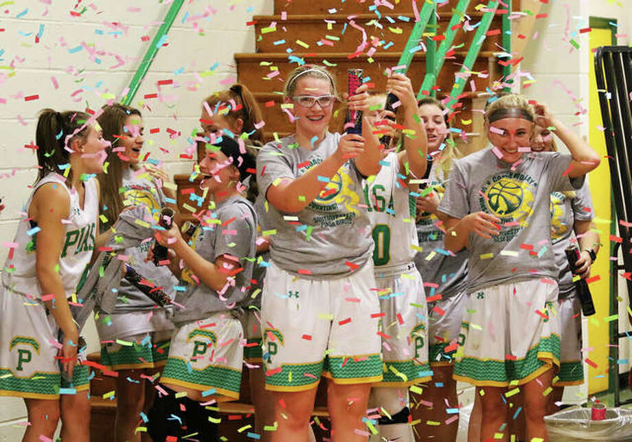 Southwestern's Annie Gallaher (middle) shoots off a confetti cannon as teammates celebrate coach Steve Wooley's 500 win Wednesday night in Piasa. Photo: Greg Shashack / The Telegraph