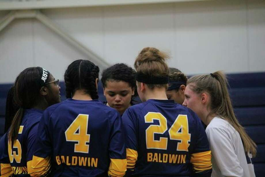 Baldwin volleyball players talk strategy during the recent district match. (Star photo/John Raffel)