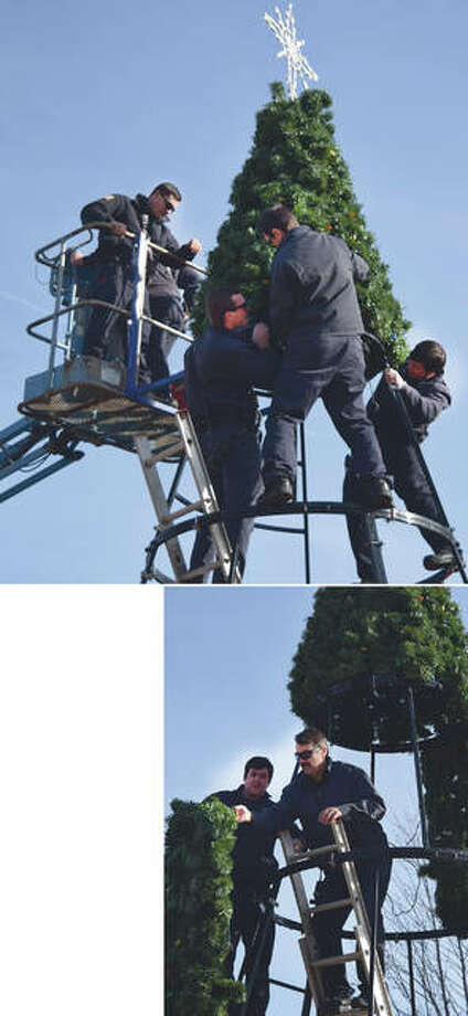 Jacksonville firefighters Chris Kesler (top, from left), Matt Leischner and Joey Hosteny set up the city's Christmas tree Wednesday on the downtown square as firefighter Eric Fair watches from a crane, ready to help his colleagues. Hosteny (at right, from left) keeps an eye on fellow firefighter Chris Kesler as he picks up a patch of Christmas tree to add to the display. Photo: Marco Cartolano | Journal-Courier