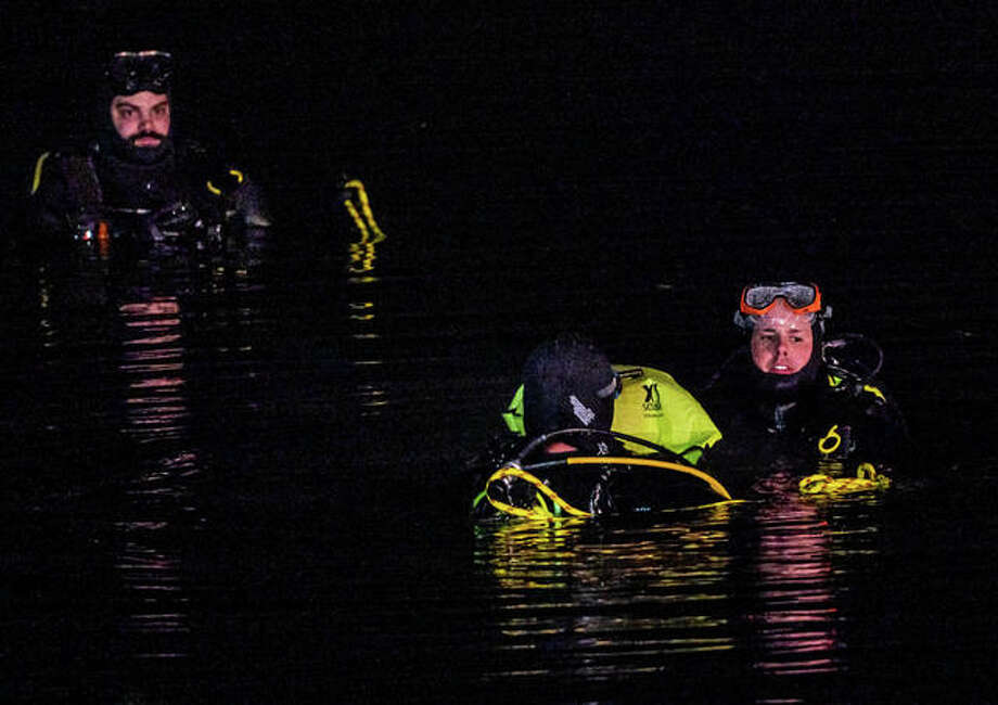 Divers from the Swansea Fire Department search a retention pond in Roxana after a vehicle was seen in the water. The bodies of a woman and a boy were recovered from the vehicle Wednesday.