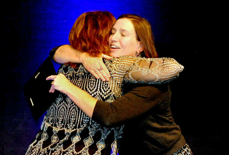 Executive Director of the Edwardsville Art Center Melissa McDonough-Borden (right) gets a hug from Kim Manoogian of Hearst Illinois as McDonough-Borden excepts the award for Best Local Art Fair won by the Edwardsville Art Fair at the Best of the Best awards at Lewis and Clark College Wednesday. Photo: Thomas Turney | For The Intelligencer