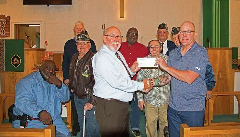 Pastor Don Wojewski (center) of the Caseville United Methodist Church presents a check to Eric Motz, of Fiddler's Green. The church welcomed area veterans during its recent service. The money comes from the Helping Hands Thrift Shop, which is a ministry of the church. Fiddler's Green, located at 2762 Pigeon Road in Bad Axe, is dedicated to helping veterans. It can be reached at www.fiddlergreenllc.com or 989-269-8688. (Submitted Photo)