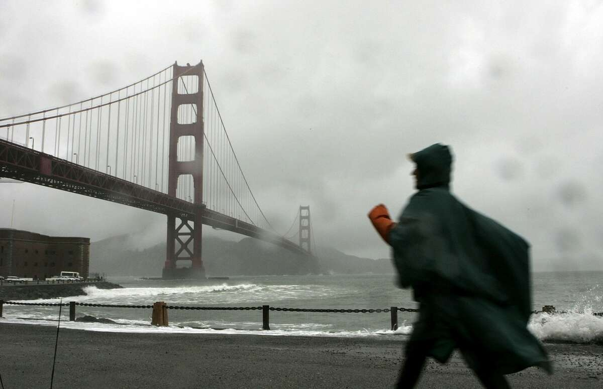 A woman walks along the seawall at Fort Point near the Golden Gate Bridge December 28, 2005 in San Francisco. A series of wet winter storms is hitting the greater San Francisco Bay Area which has prompted flood warnings and high wind advisories. The storms are expected to last through the new year.