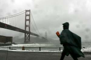 SAN FRANCISCO - DECEMBER 28: A woman walks along the seawall at Fort Point near the Golden Gate Bridge December 28, 2005 in San Francisco. A series of wet winter storms is hitting the greater San Francisco Bay Area which has prompted flood warnings and high wind advisories. The storms are expected to last through the new year. (Photo by Justin Sullivan/Getty Images)