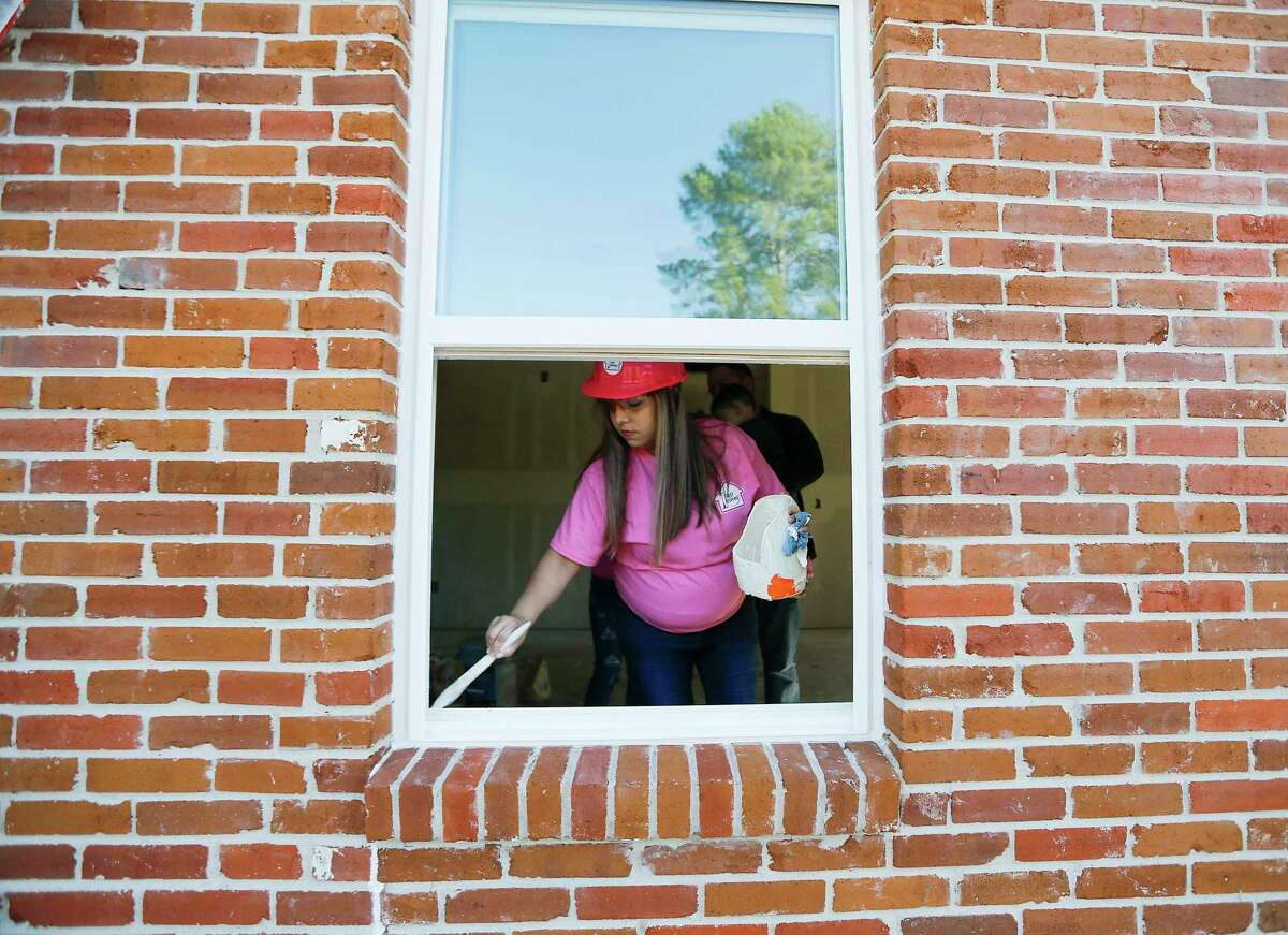 Joselyn Casas works on a Habitat for Humanity home for the media on Tuesday, Oct. 22, 2019 in Houston. Casas had to leave her home, five months pregnant, wading through waist-deep water to escape with her daughter during Hurricane Harvey. Habitat for Humanity helped the Casa family into a new home just a month after her son was born. She is now paying her luck forward, by helping to assemble a Habitat house for another pregnant mother.