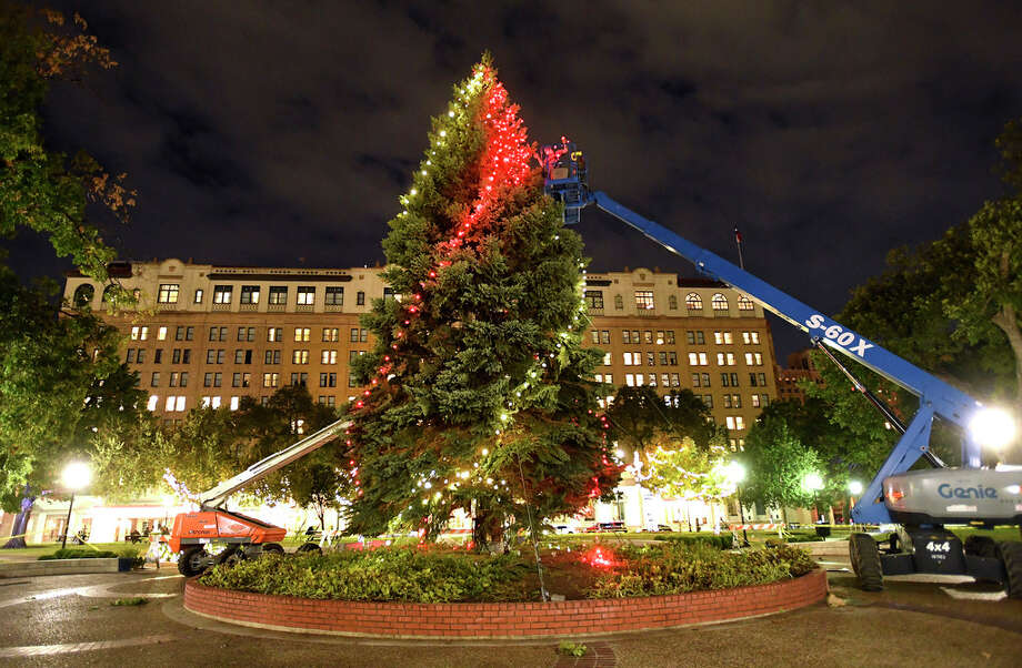 Mark Buchhorn of Carl Electric works from a cherry picker as he strings lights near the top of the H-E-B Holiday tree in Travis Park on Wednesday night, Nov. 20, 2019. The Christmas tree is a 50-foot-tall blue spruce from Northern Michigan. It will have 10,000 red and white lights. A tree-lighting ceremony is scheduled for November 29. Photo: Billy Calzada, Staff Photographer / ***MANDATORY CREDIT FOR PHOTOG AND SAN ANTONIO EXPRESS-NEWS /NO SALES/MAGS OUT/TV