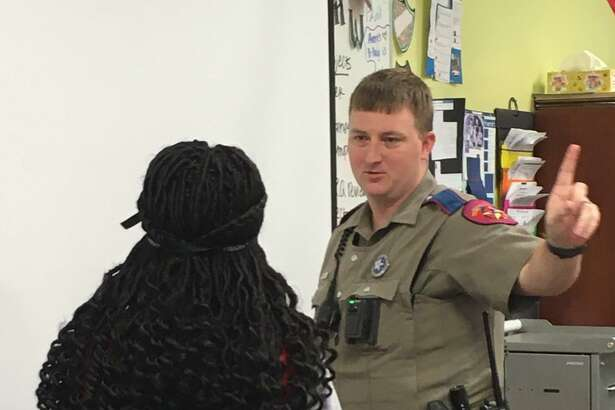 Department of Public Safety Trooper Kevin Fitzgerald demonstrates with a student volunteer fromHarmony School of Innovation-Katy what a typical traffic stop might involve after law enforcement has pulled a motorist over for suspected driving while intoxicated. Above, he tests her vision.