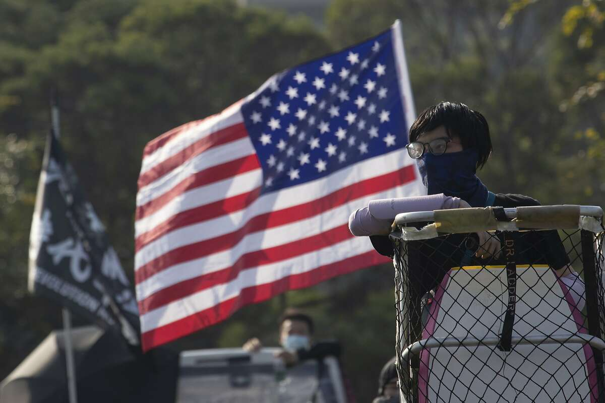 A protester watch from a lookout position near a U.S. flag on the barricaded bridge into the Chinese University of Hong Kong, in Hong Kong, Wednesday, Nov. 13, 2019. Protesters in Hong Kong battled police on multiple fronts on Tuesday, from major disruptions during the morning rush hour to a late-night standoff at a prominent university, as the 5-month-old anti-government movement takes an increasingly violent turn. (AP Photo/Ng Han Guan)