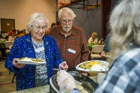 Florence Scott, left, and Dean Scott, center, are served by Jeanne Yost, right, during a community Thanksgiving meal hosted by Midland Missionary Church Wednesday, Nov. 20, 2019. (Katy Kildee/kkildee@mdn.net)