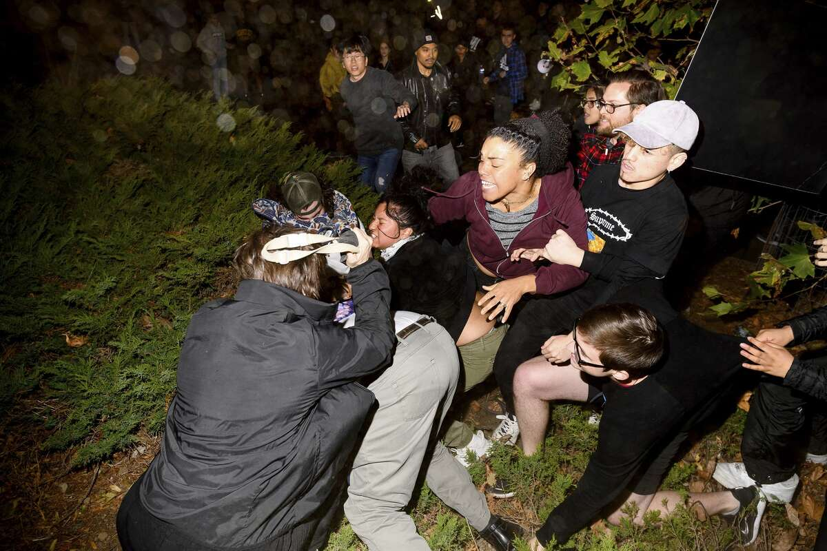 A man pushed by protesters is surrounded as he falls to the ground while leaving a speech by conservative commentator Ann Coulter at the University of California, Berkeley, Wednesday, Nov. 20, 2019, in Berkeley, Calif. Hundreds of demonstrators gathered as Coulter delivered a speech titled
