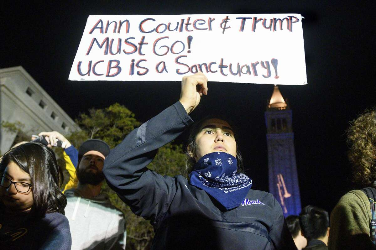 University of California, Berkeley student Magaly Mercado holds a protest sign as attendees leave a speech by conservative commentator Ann Coulter on Wednesday, Nov. 20, 2019, in Berkeley, Calif. Hundreds of demonstrators gathered on campus as Coulter delivered a talk titled