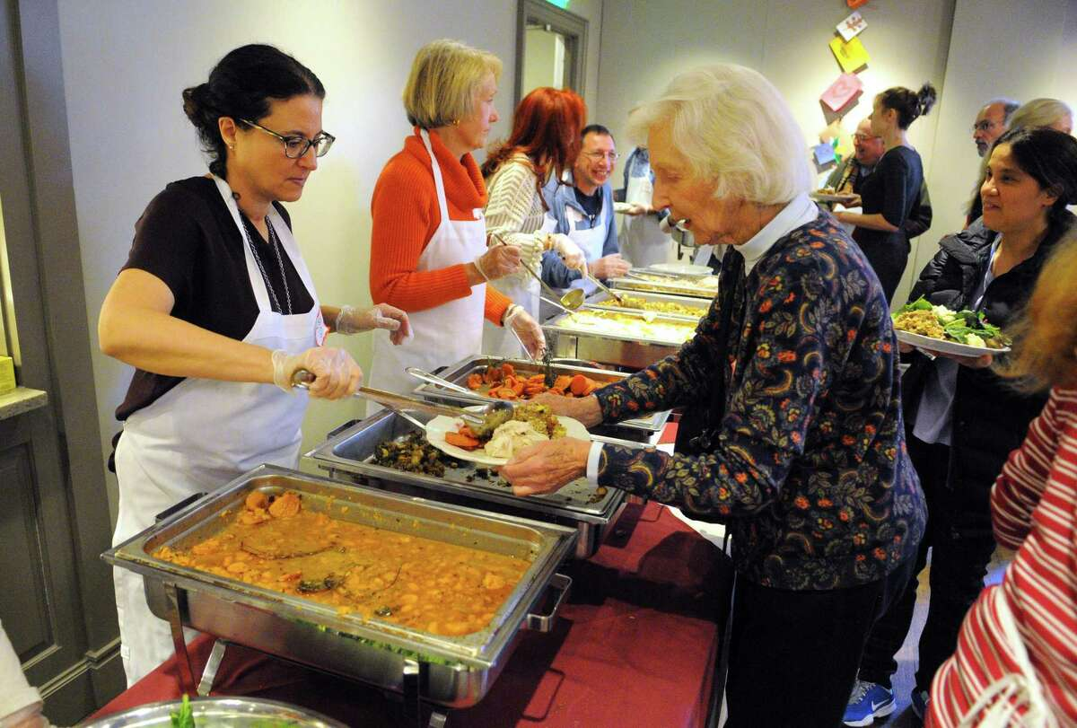 """Westport resident Jeanne Holleman is served Thanksgiving dinner during Saugatuck Congregational Church's 47th Annual Community Thanksgiving Feast in Westport, Conn., on Thursday Nov. 23, 2017. According to the church's website, """"For over 40 years, Saugatuck has been holding Community events on Thanksgiving and Christmas Day that are free and open to everyone - young families, homeless people, older folks, anyone who might otherwise be alone."""" For more information on attending or volunteering go to: http://saugatuckchurch.org/"""