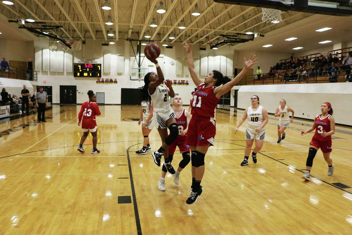 Lady Panther Drelyn Willis drives the lane and shoots a layup over Lutheran North forward Andrea Ramirez in Tuesday night's non-district clash at Liberty.