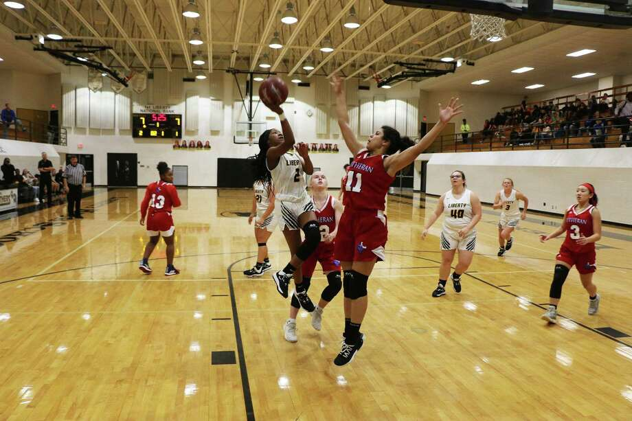 Lady Panther Drelyn Willis drives the lane and shoots a layup over Lutheran North forward Andrea Ramirez in Tuesday night's non-district clash at Liberty. Photo: David Taylor / Staff Photo