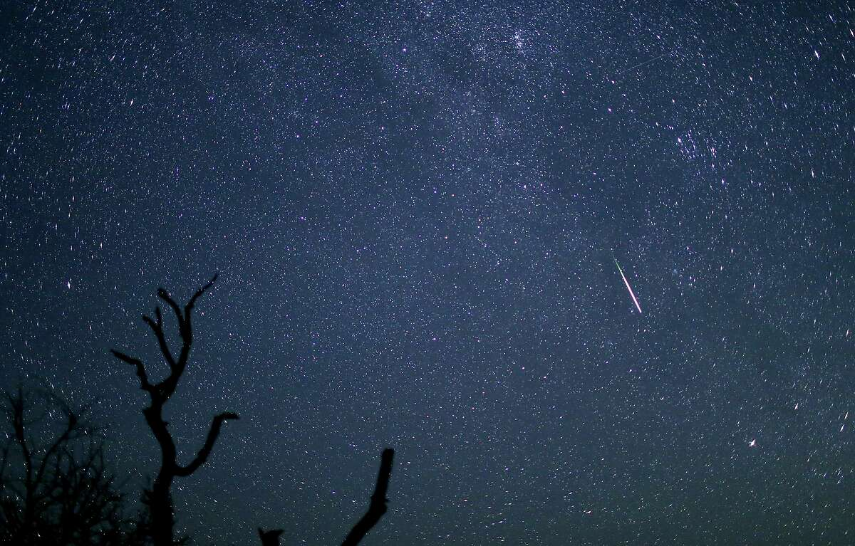 The Perseid meteor shower is clearly visible along with a meteor streaking across the sky above Enchanted Rock early on the morning of Aug. 13.