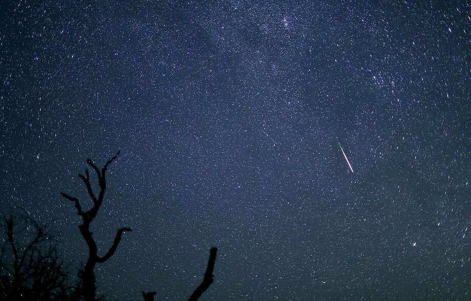 The Perseid meteor shower is clearly visible along with a meteor streaking across the sky above Enchanted Rock early on the morning of Aug. 13. Photo: Edward A. Ornelas / San Antonio Express-News / © 2015